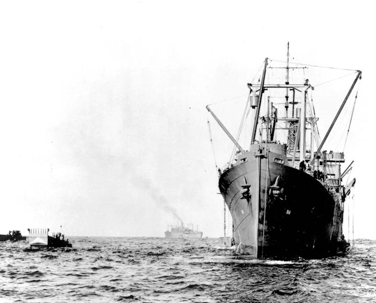 Rare photograph of the USS Hunter Liggett debarking troops for the Guadalcanal landings. Notice the use of cargo derricks to lower landing craft into the water. (U.S. Navy courtesy photo)