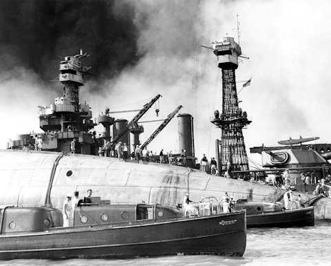 Rescue crews work on the upturned hull of the 29,000-ton battleship USS Oklahoma (BB 37) Dec. 8, 1941. The ship capsized after being struck by Japanese warplanes during the attack on Pearl Harbor Dec. 7, 1941. Holes were burned through the hull to permit the rescue of some of the men trapped below. U.S. Navy photo courtesy of the Library of Congress Archives