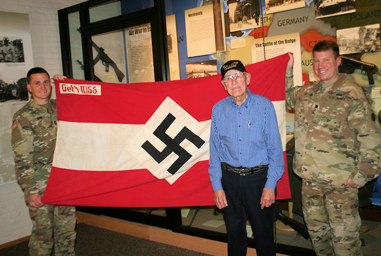 November 20, 2017 - World War II Army veteran Charlie Brown of Olean, New York displays his captured Hitler Youth battle flag from his combat experience in Europe as part of the 258th Field Artillery Battalion with Lt. Col. Peter Mehling, right, and Capt. Steven Kerr, left, the current battalion commander and operations officer of the New York Army National Guard's 1st Battalion, 258th Field Artillery at the New York State Military Museum in Saratoga Springs, New York. (U.S. Army photo by Col. Richard Goldenberg, New York  National Guard)