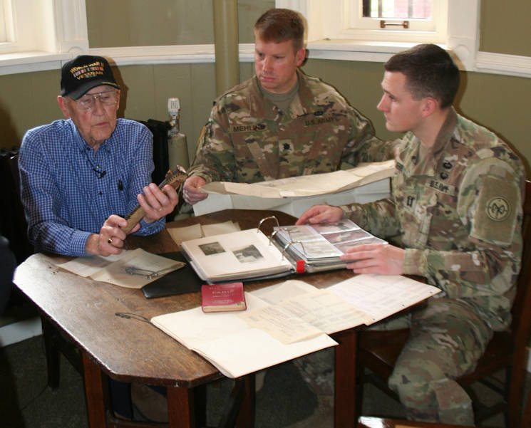 November 20, 2017 - World War II Army veteran Charlie Brown of Olean, New York discusses his experiences in Europe as part of the 258th Field Artillery Battalion with Lt. Col. Peter Mehling, center, and Capt. Steven Kerr, right, at the New York State Military Museum in Saratoga Springs, New York. Brown met with the museum director and the current Soldiers of the 258th Field Artillery to review his collection of artifacts and information about the battalion's WWII combat service.(U.S. Army photo by Col. Richard Goldenberg, New York  National Guard)