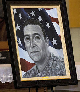 A portrait of Cpl. Adam Chitjian, 3rd Battalion, 8th Cavalry Regiment, 3rd Brigade Combat Team, 1st Cavalry Division, who was killed in action in Balad, Iraq, Oct. 25, 2007, that was presented to his wife, Shirley Chitjian, by Phil Taylor, artist for and founder of The American Fallen Soldiers Project: Portraits of Patriotism, Jan. 7, during a memorial ceremony at the 58th Street Chapel.
