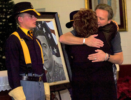 Phil Taylor, artist for and founder of The American Fallen Soldiers Project: Portraits of Patriotism, embraces Shirley Chitjian, wife of Cpl. Adam Chitjian, 3rd Battalion, 8th Cavalry Regiment, 3rd Brigade Combat Team, 1st Cavalry Division, who was killed in action in Balad, Iraq, Oct. 25, 2007, after presenting her a portrait of her husband during a memorial ceremony at the 58th Street Chapel.