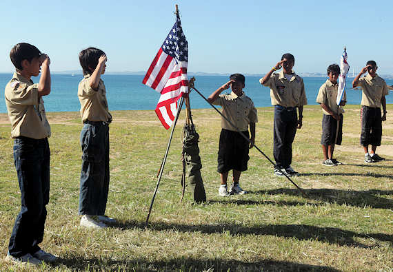 Boy Scouts render a scout salute to the American flag during the opening ceremony of the Ryukyu Rendezvous at Kin Blue Beach Oct. 29, 2011. During the rendezvous, the Boy Scouts taught the Cub Scouts the fundamentals of scouting.  Photo by USMC Lance Cpl. Erik Brooks