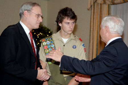 Defense Secretary Robert M. Gates speaks with Eagle Scout Adam Evans and his father, David Evans, during the Boy Scouts of America National Capital Area Council's 39th Annual Citizen of the Year Award reception and dinner in Washington, D.C., Nov. 15, 2007. Since 1968, the National Capital Area Council has annually honored those who serve as a good example and are dedicated to serving youth in America.