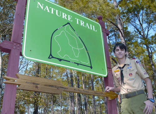 Jared R. Gillan, a Boy Scout with Boy Scout Troop 3 of Albany, Ga., showcases a new sign at one of Marine Corps Logistics Base Albany's nature trails, Feb. 4, 2012. He and more than 40 volunteers, spruced up one of the trails between Building 3500 and Maintenance Center Albany for an Eagle Scout project. Photo by Nathan Hanks