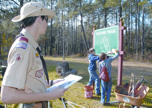 Jared R. Gillan observes Boy Scouts as they clean the sign at the nature trails entrance, Feb. 4, 2012. Photo by Nathan Hanks