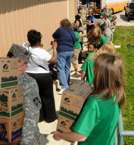 Girl Scouts, service members and volunteers help form an assembly line to unload a truck full of Girl Scout Cookies being donated to Camp Atterbury Joint Maneuver Training Center, April 9, 2012. Roughly 2,000 cases of cookies were donated to Atterbury by Girl Scouts of Central Indiana as part of Operation Cookie Drop, a nationwide Girl Scouts of America program that donates cookies to service members around the world. Photo by Army Staff Sgt. Matthew Scotten