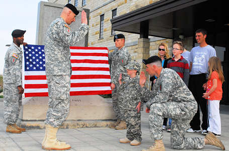 Army Col. Joseph Wawro, 4th Infantry Combat Brigade commander, enlists Ian Field, 7, with the help of Army 1st Sgt. Brandon McGuire, during a ceremony April 14, 2011, in front of 1st Infantry Division headquarters.