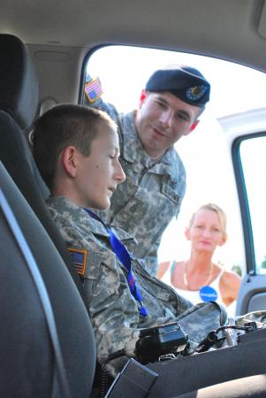 Staff Sgt. Franklin Moore, center, a native of Mayodan, N.C., explains the features of a Garrison Patrol Vehicle to Ryan Beaulieu, a child with the Make a Wish Foundation while his mother looks on. Moore, a Military Police Investigator with the 16th Military Police Brigade, escorted Beaulieu and his Family when they visited Fort Bragg. Photo by Capt. Thomas Cieslak