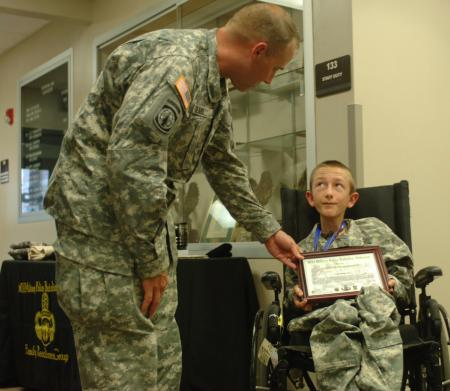 Maj. Jeffrey Searl, left, the executive officer of the 503rd Military Police Battalion (Airborne), 16th Military Police Brigade and a native of Mukwonago, Wis., bestows honorary membership of the battalion upon Ryan Beaulieu, a child with the Make a Wish Foundation. Photo by Spc. Garett Hernandez