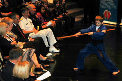 Tristan Fissette, 10, demonstrates his black-belt karate form for the audience at the Our Military Kids of the Year awards ceremony at the Navy Memorial in Washington, D.C., April 14, 2011. Tristan, whose father serves in the Navy Reserve, was one of four children honored by Our Military Kids, a nonprofit organization that provides artistic, athletic and educational grants to children of deployed National Guardsmen and military reservists. U.S. Navy photo by Petty Officer 2nd Class Patrick Gordon