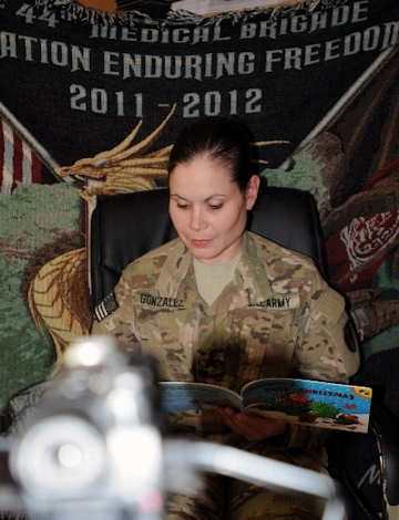 U.S. Army Sgt. Madelyn Gonzalez, of Aguada, Puerto Rico, a paralegal for Task Force 44th Medical Brigade, reads a book to her 3-year-old son at Bagram Air Field with the help of the United Through Reading program Nov. 19, 2011. Photo by Army Spc. William Begley