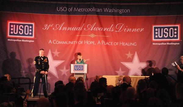 USO Gala Awards Dinner (March 14, 2013) - Kathleen Causey, recipient of the USO's Col. John Gioia Patriot Award, with husband, Army Sgt. 1st Class Aaron Causey, on stage behind her, points to the table where the pair's parents are sitting. Causey lost both of his legs above the knee and sustained multiple injuries to his hands and arms in 2011. DOD photo by Air Force Master Sgt. Chuck Marsh