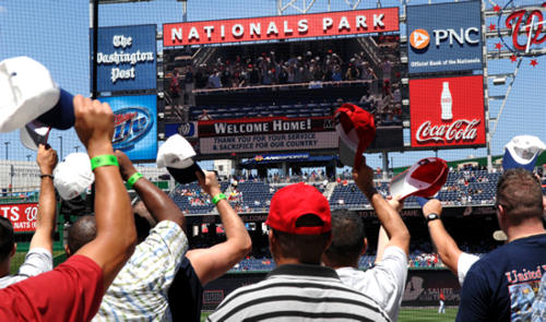 Wounded warriors and military family members raise their hats during a special salute to troops at the Washington Nationals-San Francisco Giants game in Washington, D.C., July 11, 2010.