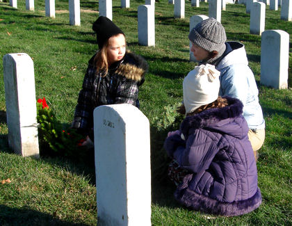 A mother talks to her daughters about the value of freedom after they placed a wreath on a grave during Wreaths Across America at Arlington National Cemetery, Dec. 12, 2009. This was the 18th year that the Maine-based Worcester Wreath Company has donated wreaths to honor our country's fallen servicemembers.