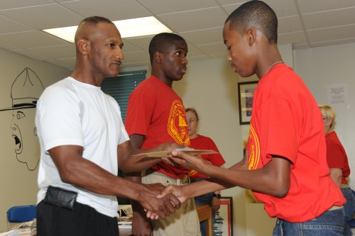 Nathaniel Lowman, commanding officer, 2nd Battalion of Georgia, (left) shakes hand with a newly-promoted Albany Young Marine, as Staff Sgt. Corey Chism, (center) reads the citation on July 17, 2010.