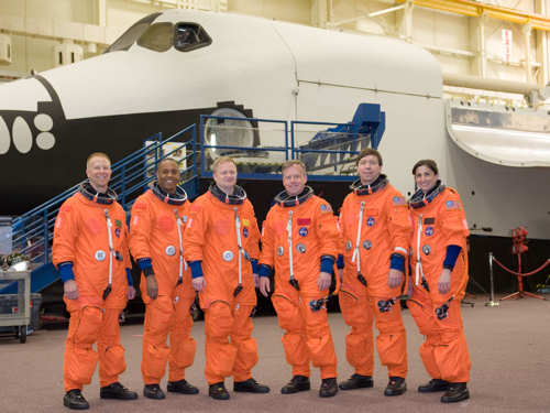 Attired in training versions of their shuttle launch and entry suits, the STS-133 crew members take a brief break for a portrait in the Space Vehicle Mock-up Facility at NASA's Johnson Space Center on March 31, 2010. From the left are NASA astronauts Tim Kopra and Alvin Drew, both mission specialists; Eric Boe, pilot; Steve Lindsey, commander; Michael Barratt and Nicole Stott, both mission specialists. NASA photo