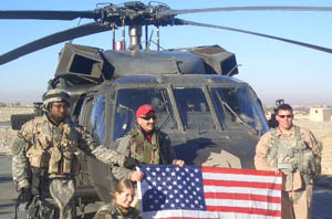 Aaron in Iraq with troops with flag in front of chopper