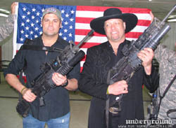 Troy and Eddie posing with weapons in front of flag held by troops during 2006 USO tour in Iraq
