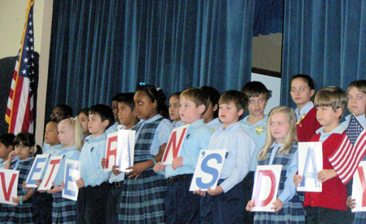Our Lady of Lourdes Catholic school students holding letters that spell... Veterans Day