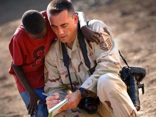 U.S. Air Force Master Sgt. Scott Wagers, a photographer from Combined Joint Task Force - Horn of Africa, writes down the name of an orphan after taking his photograph in Djibouti City, Djibouti, Dec. 12, 2006.