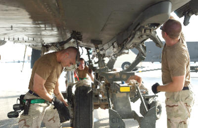 (From left) Staff Sgt. Warren Johnson, Senior Airman Paul Moore, Staff Sgt. Dave Kelley and Staff Sgt. Kiel Nichols install a fuel tank on an F-15E Strike Eagle at a forward-operating base in Southwest Asia Sept. 1. The Airmen are crew chiefs deployed from the 335th Aircraft Maintenance Unit at Seymour Johnson Air Force Base, N.C.