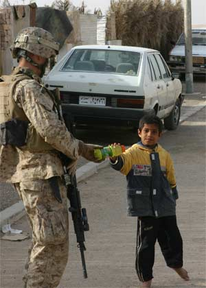 An Iraqi boy peers tentively at the camera as a Marine from Alpha Co., Battalion Landing Team 1st Bn., 2nd Marines gives him a bottle of Gatorade during a security patrol near Forward Operating Base New Market, Jan. 2, 2006.  BLT 1/2 is the ground combat element of the 22nd Marine Expeditionary Unit (Special Operations Capable), which is conducting counterinsurgency operations with the 2nd Marine Division in Iraq's Al Anbar province. Photo by: Lance Cpl. Peter R. Miller