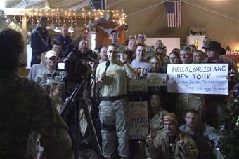 KUKRUK AIR BASE, Iraq (AFPN) -- Airmen and Soldiers of the 506th Air Expeditionary Group and 1st Brigade Combat Team crowd in front of a video camera before the 2006 Rose Bowl game