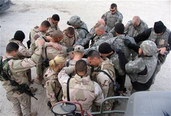 Airmen and Soldiers take a moment to pray for each other's safety before heading out for another day of convoy duty in Iraq. The Airmen run the convoys into Iraq and the Soldiers, in their armored trucks, escort them.