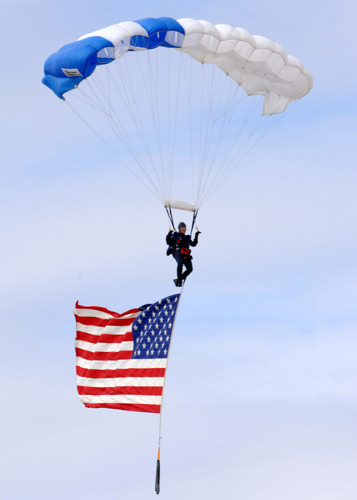 "Cadet 1st Class Ilea Eskildsen, U.S. Air Force Academy's Wings of Blue Parachute Demonstration Team, parachutes down to Luke Air Force Base, Ariz., with the American Flag during the ""The Show of Force 2007, From Heritage to Horizons Air Show"" March 24, 2007."
