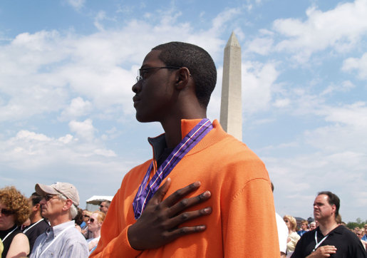 "Quincy Jallah, son of a fallen soldier, honors the presentation of colors during the ""Time of Remembrance"" ceremony, May 20, 2007, near the Washington Monument. More than 3,100 families and friends of service members lost in Iraq and Afghanistan gathered to remember their loved ones."