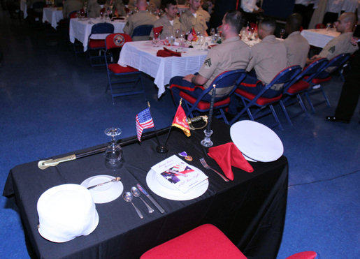 This is the traditional empty chair and lone table draped in black set at the mess night for fallen Marines who are unable to attend the mess. The single lighted candle represents the flame of eternal life. The Purple Heart Medal reflects the shedding of blood and the ebb of life in battle. The identification tags are blank but could bear the name of any Marine present. The inverted dinner setting represents the fallen Marines breaking bread with the mess in spirit only.