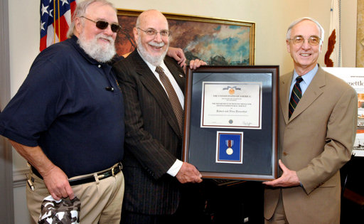 "Deputy Defense Secretary Gordon England (right) presents the Department of Defense Medal for Distinguished Public Service to Robert Rosenthal (center), founder of the ""Spirit of America Tour,"" which brings entertainers to military installations around the nation. Singer Charlie Daniels, of the Charlie Daniels Band -- one of the groups involved in the ""Spirit of America Tour,"" also participated."