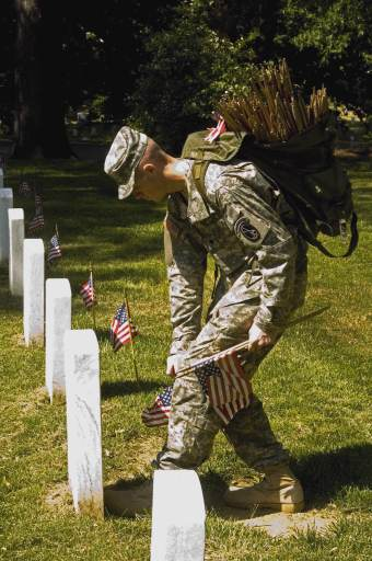 "U.S. Army Spc. Chase Neely places flags in front of headstones at Arlington National Cemetery in Arlington, Va., May 24, 2007, for Memorial Day. Neely is a Tomb Sentinel from the 3rd U.S. Infantry Regiment ""The Old Guard."""