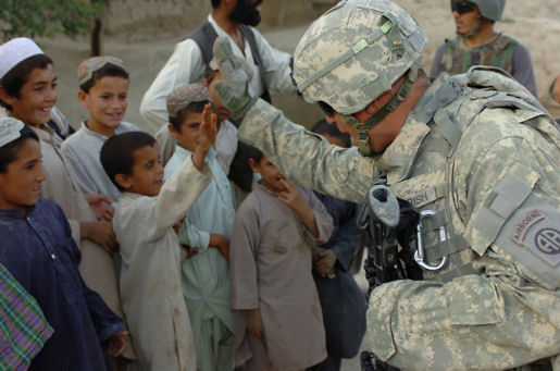 "Communicating through means other than talking, Sgt. 1st Class Matthew S. Parrish demonstrates the art of ""high-fiving"" to a group of Afghan kids, July 16, 2007 while visiting Hassan village in the Gelan District, Ghazni Province, Afghanistan."
