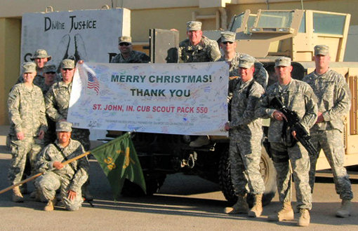 Members of the 32nd MP Detachment in Iraq hold up a Christmas Tribute Banner they received as part of a holiday shipment from Treats and Letters on December 11, 2007. The shipment also included care packages and nearly 2,000 Christmas cards. The Christmas banner was sponsored by Cub Scout Pack 550 of St. John, Ind.