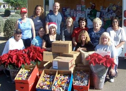 Arizona's Operation Stocking Stuffer team and a team from local business Denco Dental rest in front of a donated U-Haul truck, loaded with $2,500 worth of donated gifts and 400 pounds of candy for Christmas stockings to be shipped to Marines in Iraq.