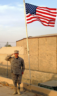 "Master Sgt. William ""Spanky"" Gibson saluting with flag in background"