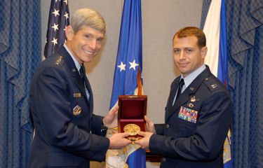 Air Force Chief of Staff Gen. Norton Schwartz presents Capt. Daniel Santoro with the Cheney Award Oct. 8, 2009 at the Pentagon. Captain Santoro's leadership and foresight led his squadron to successfully complete 29 missions, delivering 95 passengers and 211 tons of humanitarian aid to the war-torn country of Georgia, following an August 2008 Russian invasion. Capt. Santoro is a C-130E Hercules instructor pilot and the chief of tactics assigned to the 37th Airlift Squadron at Ramstein Air Base, Germany.