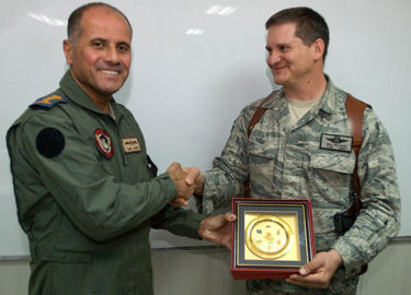 Iraqi air force Col. Sami Saeed shakes hands with Air Force Lt. Col. Bill Iuliano during a brief ceremony at Contingency Operating Base Basra, Iraq, Sept. 14, 2009. The two officers flew on opposite sides of the Persian Gulf War in 1991, but have worked together in Operation Iraqi Freedom to strengthen the Iraqi air force.