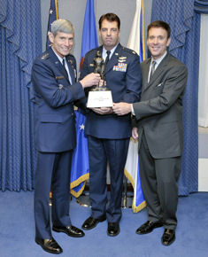 Air Force Chief of Staff Gen. Norton Schwartz assisted by Koren Kolligan presents Lt. Col. Booth M. Johnston with the Koren Kolligian Jr. Safety Trophy June 16. He received the award for an October 2007 incident in which he suffered a severe back and neck injury during a high-G maneuver. Despite the near total loss of use and lack of sensation in his hands and feet, Colonel Johnston was eventually able to level the aircraft and land at Ellington Field, Texas.