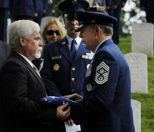 Chief Master Sergeant of the Air Force Rodney J. McKinley presents a flag to retired Chief Master Sgt. Dale Airey, during the memorial service for his father Chief Master Sgt. Paul W. Airey at Arlington National Cemetery, Va., May 28, 2009.