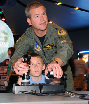 "Pilot in training Cooper Hirst of Ogden, Utah, gets a little help with the controls of a flight simulator from Lt. Col. Paul ""Buster"" Delmonte, 466th Fighter Squadron pilot, before the IMAX showing of ""Fighter Pilot: Operation Red Flag"" at the Clark Planetarium during Air Force Week Salt Lake City June 2, 2009."