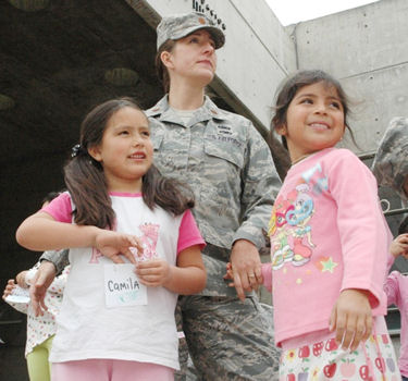 Maj. Jana Nyerges waits with children from the Angels Community Center outside a museum prior to sponsoring the children's admission to the science exhibits Oct. 13, 2009, in Santiago, Chile. Airmen decided to use their first day in Chile to sponsor a group of at-risk children during a visit to the museum. Major Nyerges is a member of Air Forces Southern participating in a subject matter exchange with the Chilean air force.