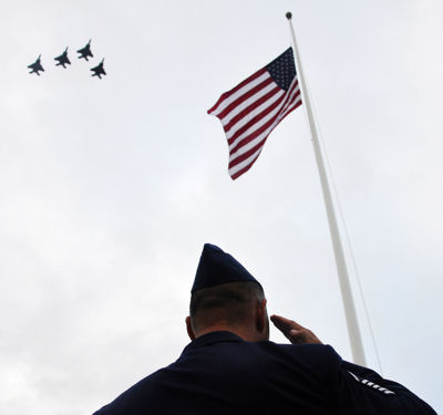 Master Sgt. John Sieh salutes the flag as F-15 Eagles fly a missing man formation Dec. 7, 2009, during the 68th Remembrance Ceremony at Hickam Air Force Base, Hawaii. The ceremony marked the anniversary of the Dec. 7, 1941, attacks on Pearl Harbor Navy fleet and the Army Air Corps fields of Hickam, Wheeler and Bellows. Sergeant Sieh is from the 15th Airlift Wing protocol office and the F-15s are from the 199th Fighter Squadron, Hawaii Air National Guard.