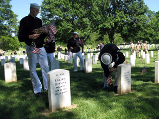 "Navy Seaman Josh Sallee, left, and Seaman Mark Matthews, placing a flag by a grave marker, participate with fellow U.S. Navy Ceremonial Guard members in the annual ""Flags In"" tribute at Arlington National Cemetery, May 21, 2009."