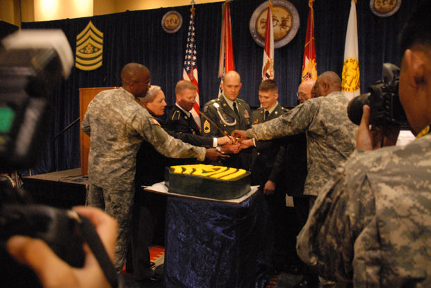 Sgt. Maj. of the Army Kenneth O. Preston holds the sword along with NCO of the Year Sgt. 1st Class Aaron Beckman and Soldier of the Year Spc. Clancy Henderson as they partake in the ceremonial cutting of the cake at the 8th Annual Awards Luncheon at the Association of the United States Army annual meeting Oct. 5, 2009.