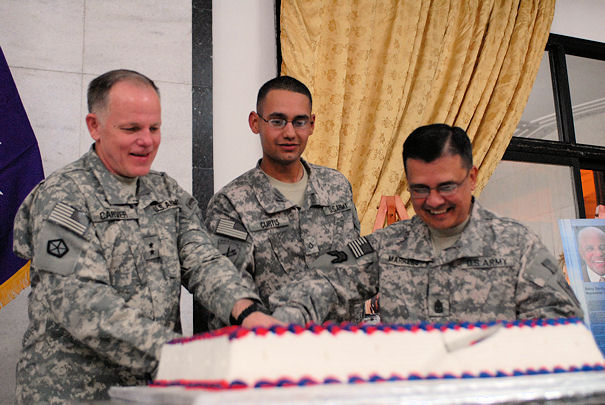 Chief of Chaplains Maj. Gen. Douglas Carver (left), Pfc. Cody Curtis, a chaplain assistant with the 16th Psychological Operations Task Force (center) and Chief of Chaplains and Regimental Sgt. Maj. Tommy Marrero, cut a cake Nov. 25, during the 100th anniversary of the chaplain assistant celebratory dinner at Camp Victory's Joint Visitors Bureau in Baghdad, Iraq.