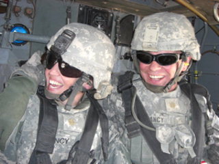 Army Lt. Col. Hailey Clancy, left, and her husband, Army Maj. Michael Clancy, share a laugh while flying to Camp Striker, Iraq, Aug. 8, 2008. The couple has served two deployments to Iraq together.