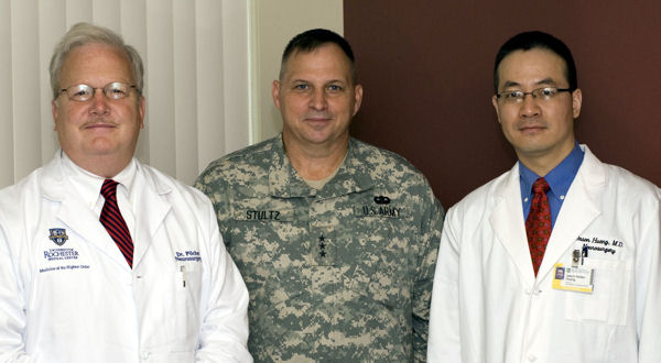 Maj. (Dr.) Jason Huang, right, an Army Reserve neurosurgeon who's become a national leader in traumatic brain injury research, discusses his work with Army Lt. Gen. Jack C. Stultz, chief of the Army Reserve, center, and Dr. Webster Pilcher, a fellow neurosurgeon at Strong Memorial Hospital in Rochester, NY.